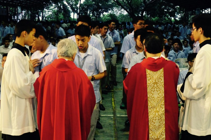 Frs. Alberto Ampil SJ and Tony Pabayo SJ give communion to high school students in the Mass of the Holy Spirit.