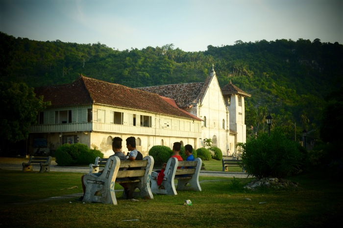 Four young boys sit on a bench on an early Sunday at their old church. Boljoon, Cebu. Photo: Fr. Jboy Gonzales SJ