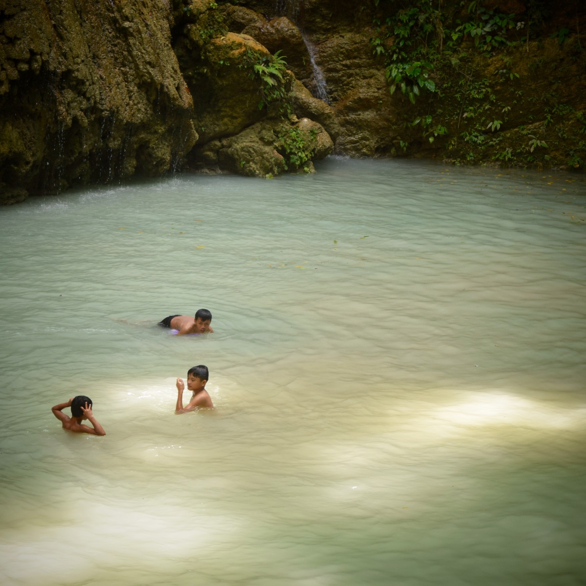 Kids swim and play in the shallow basin of Tumalog Falls. 23 August 2015