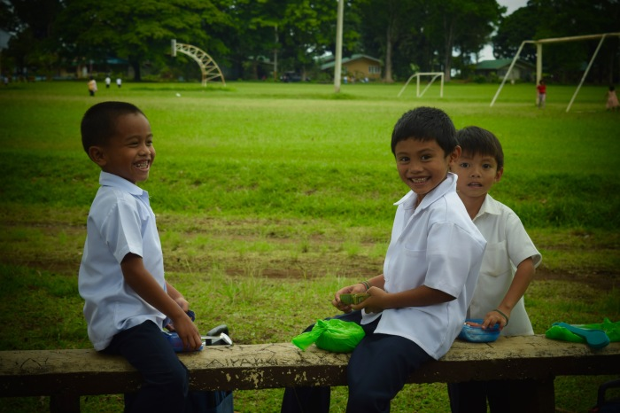 Children take their lunch break at one of the benches at the Camp Philips Soccer Field. Photo: Fr. Jboy Gonzales SJ