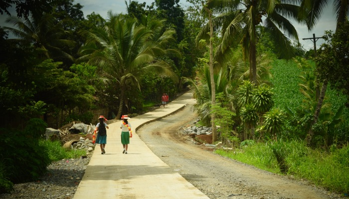 Two girls walk towards their school carrying flower garlands used for a Philippine cultural dance. Photo: Fr. JBoy Gonzales SJ
